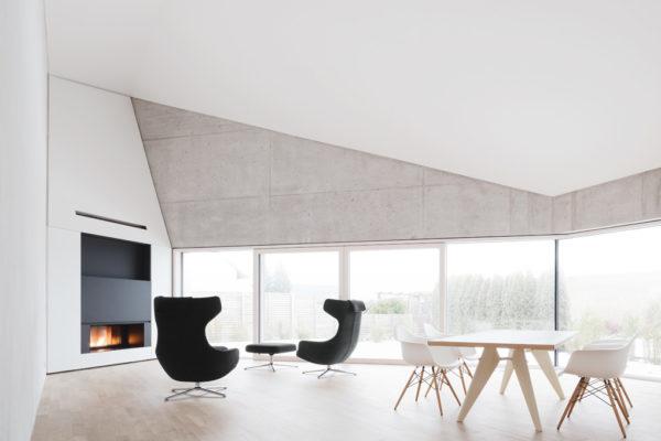 Im Obergeschoss befindet sich das Wohn-Ess-Zimmer. Der großzügige Raum ist hell. die decken sind ge- faltet. glatt ausgeführte Betonoberflächen stehen im Kontrast zu den sÄge- rauen Betonflächen der Aussenseiten.