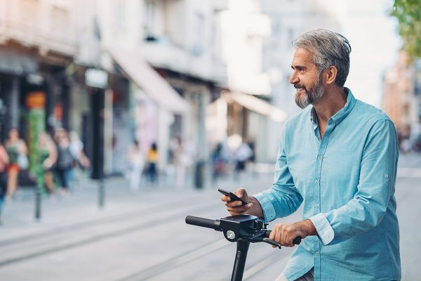 Smiling mature man with smart phone and electric scooter